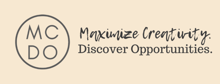 "Thin ring with letters M-C-D-O inside the ring in block text on left side of image; the words ""Maximize Creativity."" in script text on the top right side of the image, and ""Discover Opportunities."" written underneath. All text is written in dark grey with brown undertones, and the image background is beige."